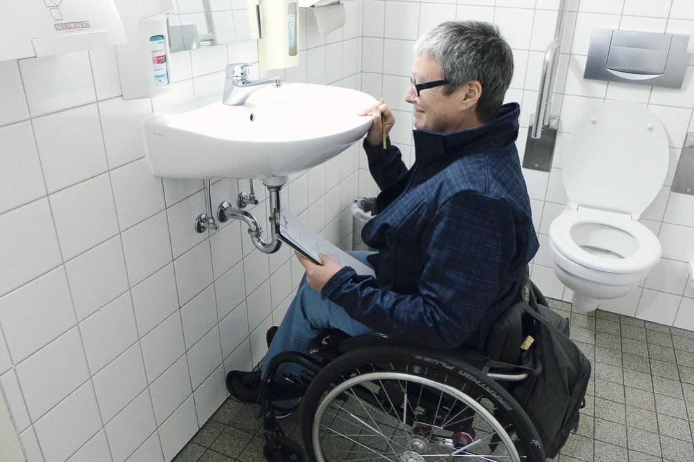 Projektleiterin Kerstin Hagemann vor einem nicht rollstuhlgerechten Waschbecken. Barrierescouts werden demnächst in Praxen überprüfen, welche Erleichterungen es dort für Behinderte gibt. Foto: ©Patienten-Initiative