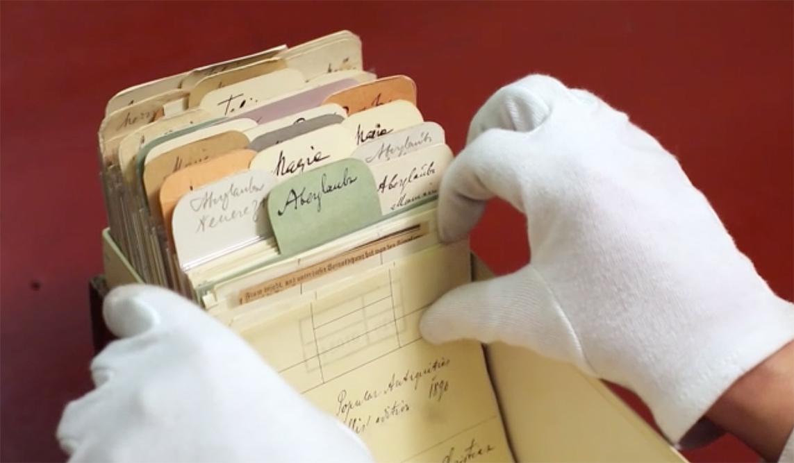 Eine Hand mit weißem Handschuh blättert in einem Karteikasten.