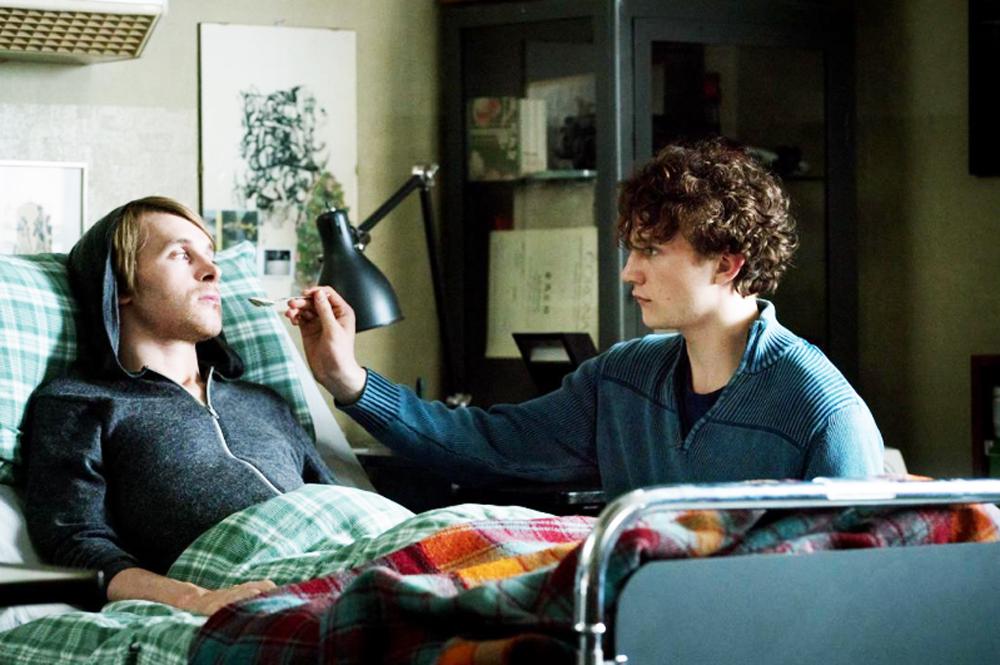 Ein junger Mann sitzt am Bett eines kranken Mannes und füttert ihn.
