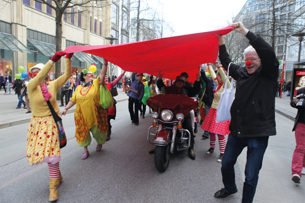 Das Bild zeigt Clowns, die bei der Konfetti-Parade einen roten Teppich halten.